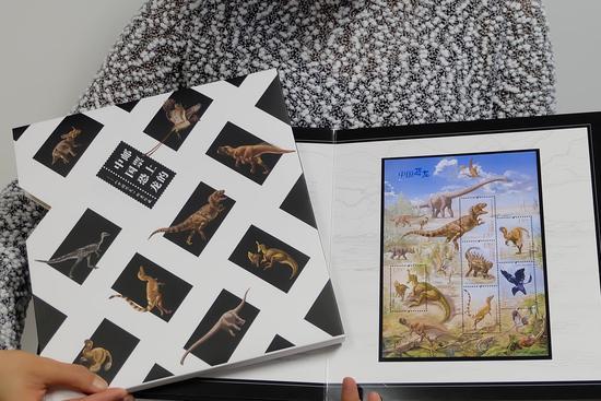 工作人员展示《邮票上的中国恐龙》邮票册